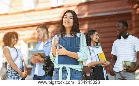 Loans For Education Concept. Portrait Of Happy Asian Student Girl Posing Outdoors In Campus With Her
