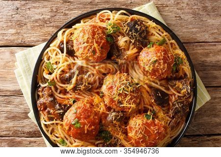 Spicy Spaghetti With Meatballs And Mushroom Gravy Close-up In A Plate. Horizontal Top View