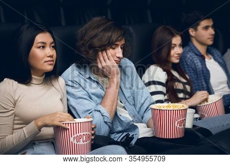 Boring Movie. Handsome Young Man Feeling Bored While Watching Film In Cinema