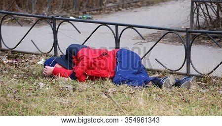 A Drunken Tramp In Sportswear Sleeps On The Lawn, Ulitsa Podvoyskogo, Saint Petersburg, Russia, Marc