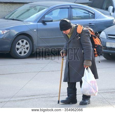 A Homeless Tramp With A Stick Walks Through The Parking Lot, Bolshevikov Avenue, Saint Petersburg, R
