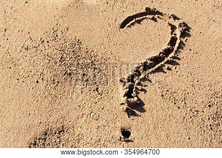 Question Mark Sign On Sand Beach Near The Sea. Concept Of Dilemma, Answer And Question