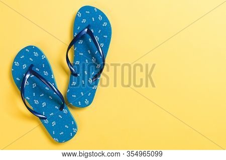 Blue Flip Flops On Yelow Background. Top View With Copy Space