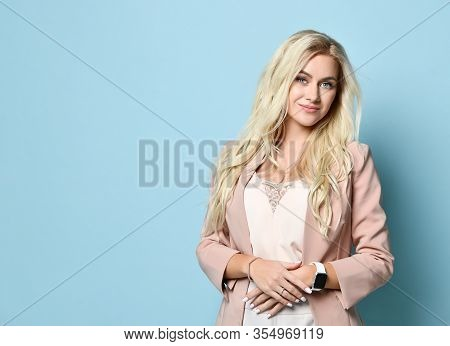 Gorgeous Blonde Girl In Beige Jacket And White Overall. There Is Watch On Her Hand. Smiling, Folded