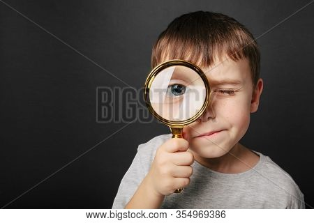 Child see through magnifying glass on the black backgrounds. Big kid eye