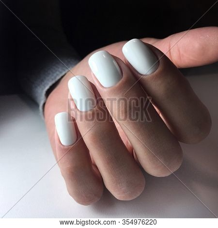 Woman's Hands With White Nails On The Dark Background