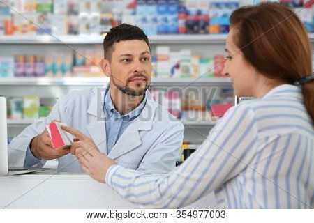 Professional Pharmacist Giving Medicine To Customer In Drugstore