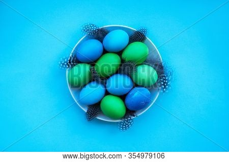 Flatlay With Dyied On Green And Blue Easter Eggs And Feather On The White Plate Isolated On Bright B