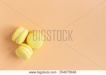 Yellow French Macarons On A Peach Pastel Background. Lemon Macarons. Flat Lay. Place For Text.