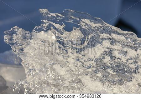 Ice Floe On The Edge Of The Coastline Against The Background Of Water. Thin Ice Near The Shore Of Th