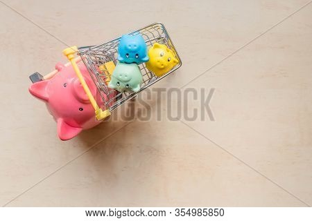 Big Pig Bank Holding Shopping Cart With Little Pigs Banks On Wood Background. One Big Pig Bank Rolli