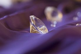 Luxury Valuable Gemstones Diamonds On Purple Silk Decoration. Symbol Of Upper Class Wealth. Big Flaw