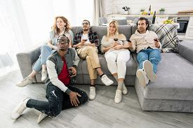 Group of young friends relaxing on couch in living-room while having red wine and watching tv at home party