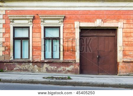 Facade Of An Old Building With Two Windows And  Door