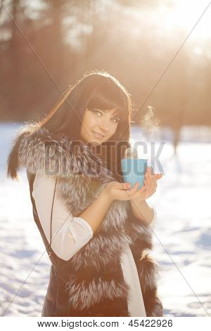 Young woman with a cup of hot drink in winter wood