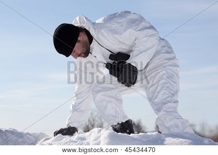 Wounded Soldier In White Camouflage Sneaking Through The Mountains