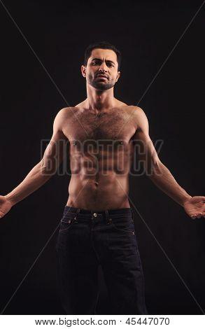 Shirtless Man On Dark Background Gesturing