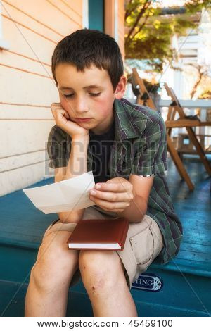 young boy reading letter on home steps