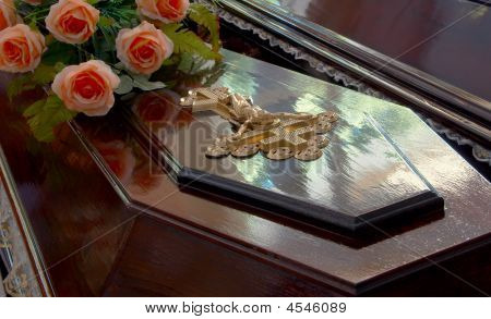 Dark wooden coffin with Jesus crucifix and roses poster