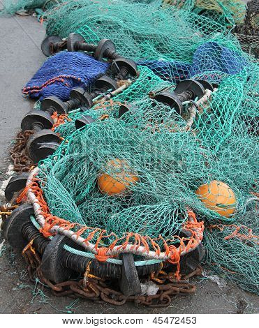 Some Fishing Nets and Floats Laying on a Quayside. poster
