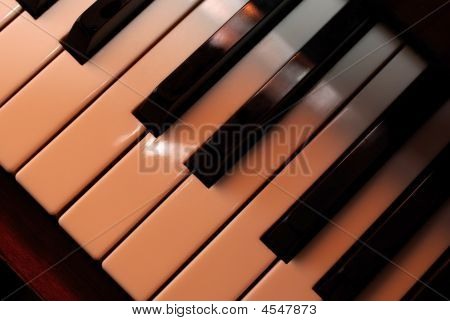 Piano Keys Close Up Using Warm Filter. Playing With Light.