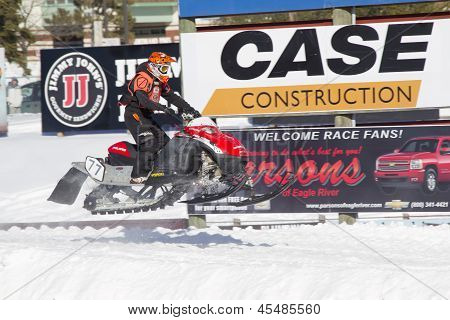 Red And Black Polaris Vforce Snowmobile Racing In Air