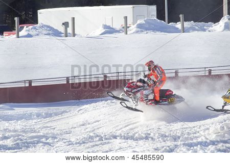 Red And Black Polaris Snowmobile Racing Over Jump