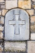 Stone cross built in old medieval wall poster