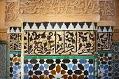 Detail of vivid blue black red and white tiles and carved stone ocher colored calligraphy in mosque Marrakesh Morocco poster