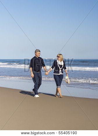 Sportive Mature Couple Walking Along The Beach