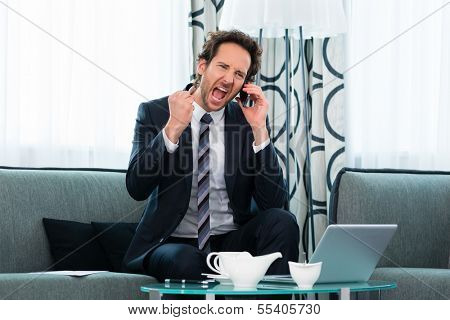 Businessman working in business hotel, he discusses some documents with a customer on the phone and is pleased about the success