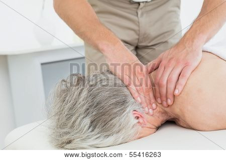 Close-up of a physiotherapist massaging a senior woman's neck in the medical office