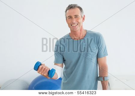 Portrait of a smiling mature man with crutch and dumbbells at the gym hospital