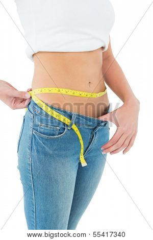Close-up mid section of a young woman measuring waist in a big sized jeans over white background