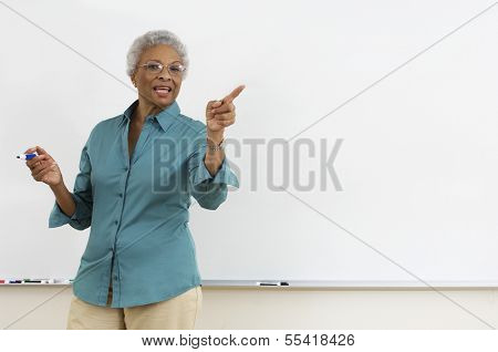 Senior teacher pointing while gesturing against white board in classroom