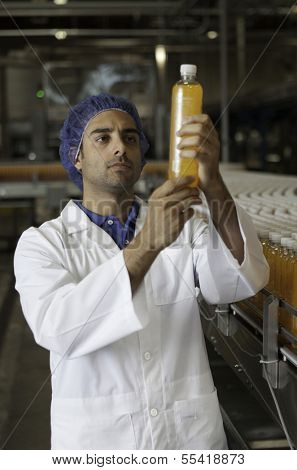 Mid adult industrial worker examining bottle in factory
