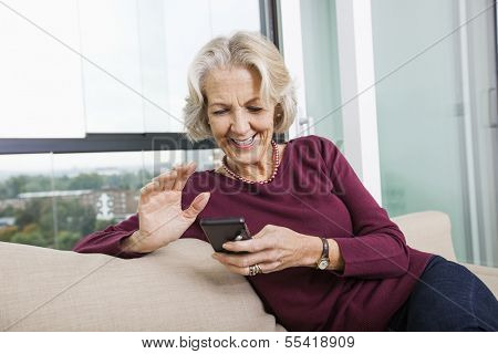 Happy senior woman text messaging through smart phone on sofa at home