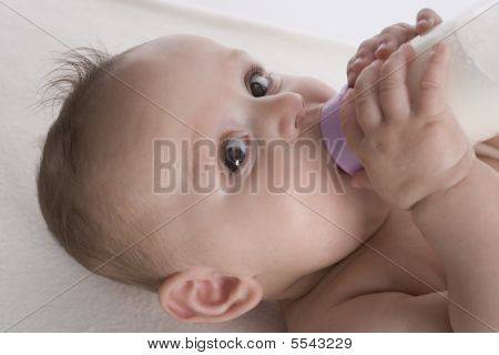 Baby is drinking milk from a baby bottle by herself