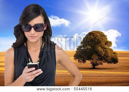 Composite image of happy attractive brunette using smartphone poster