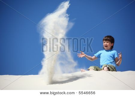 Boy Sits On Sand And Scatters It