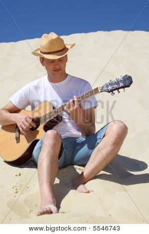 Guy In Straw Hat Plays Guitar Sitting On Sand