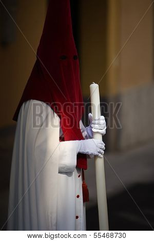 Detail penitent white holding a candle during Holy Week