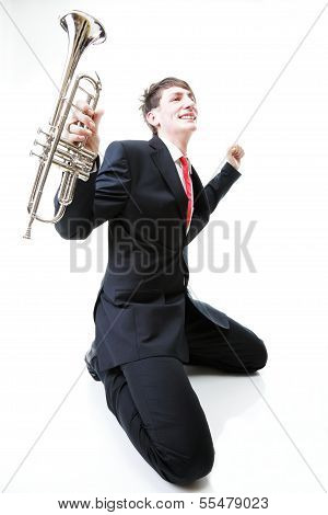 Excited Man Kneeling With Trumpet In Hand And Screaming. Isolated
