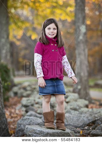 Pretty Girl Portrait In The Park Climbing On Rocks