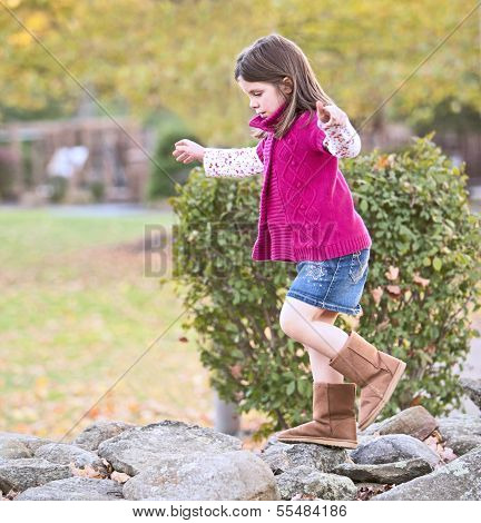 Pretty Girl Climbing On The Rocks At The Park