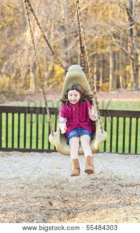 Pretty Girl Swinging In The Park With A Big Smile