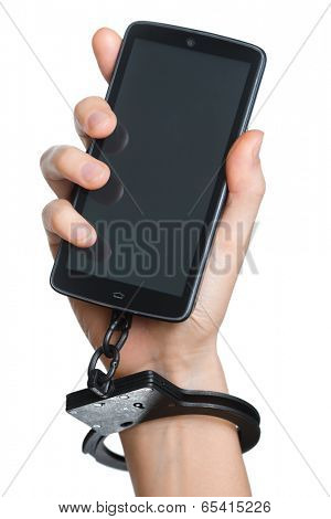 Mobile phone addiction concept. Smart phone chained to handcuff in hand isolated on white.