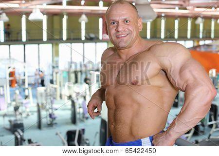 Happy shirtless sunburnt bodybuilder stands in big modern gym hall