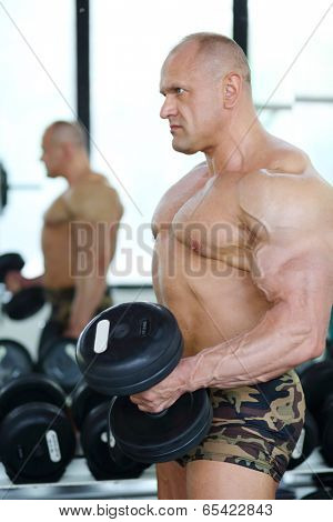 Middleaged bodybuilder in shorts raises dumbbells near mirror