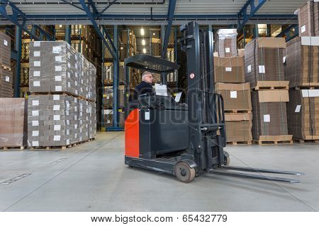 Reach truck driving around cardboard boxes in a warehouse.